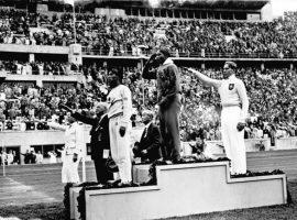 Olympische Spiele 1936 in Berlin, Siegerehrung im Weitsprung: Mitte Owens (USA) 1., links: Tajima (Japan) 3., rechts Long (Deutschland) 2., Zentralbild/Hoffmann Bundesarchiv, Bild 183-G00630 / CC-BY-SA 3.0