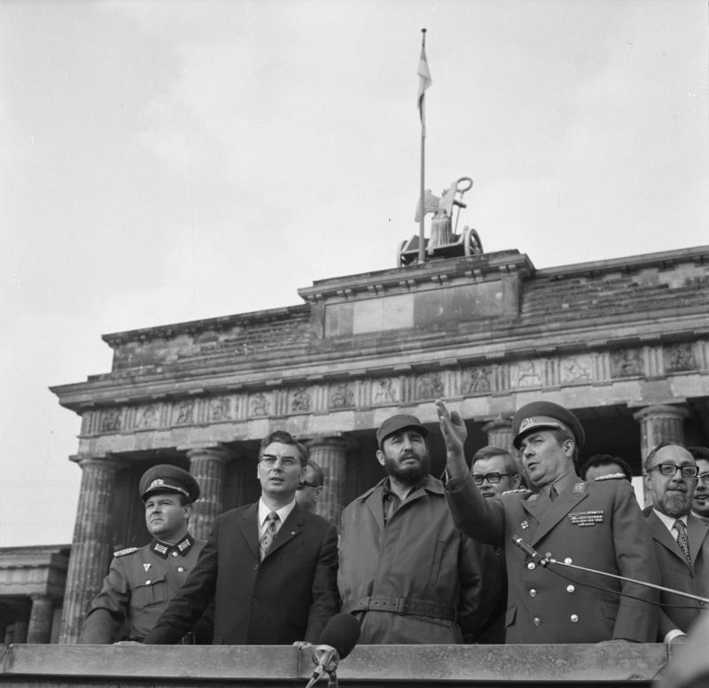Berlin: Castro / Die Partei- und Regierungsdelegationen unter Leitung des Ersten Sekretärs der KPK und Ministerpräsidenten der Revolutionären Regierung der Republik Kuba, Fidel Castro(M), besichtigte am 14.6.1972 die Staatsgrenze der DDR zu Westberlin. Die Delegation, von Werner Lamberz, Mitglied des Politbüros und Sekretär des ZK der SED (2.v.l.), und anderen Persönlichkeiten, begleitet, wurde von Generalleutnant Arthur Kunath, Satdtkommandant von Berlin (2.v.r.), informiert. Rechts: Carlos Rafael Rodriguez, Mitglied des Sekretariats des ZK der KPK und Minister der Revolutionären Regierung. Bundesarchiv, Bild 183-L0614-040 / CC-BY-SA 3.0 [CC BY-SA 3.0 de (http://creativecommons.org/licenses/by-sa/3.0/de/deed.en)], via Wikimedia Commons