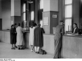 Foto: Halle. Bank- und Sparkassenbetrieb in Halle nach der Währungsreform im Westen. Auch am Montag, dem 24.6. war der Kassenbetrieb in Halle überall normal. U.B.: Eine Filiale der Sparkasse während der Schalterstunden. Foto: Paalzow, Halle -SNB- Bundesarchiv, Bild 183-V06526 / Paalzow, Günther / CC-BY-SA 3.0 [CC BY-SA 3.0 de (https://creativecommons.org/licenses/by-sa/3.0/de/deed.en)], via Wikimedia Commons