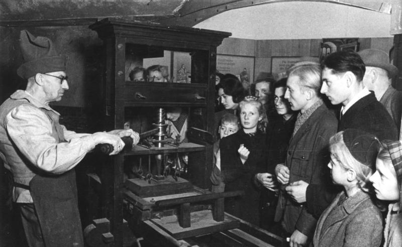 Das Bild zeigt einen Drucker in historischer Berufstracht an der Gutenbergpresse. Bild von Bundesarchiv, Bild 183-R67584 / CC-BY-SA 3.0 [CC BY-SA 3.0 de (https://creativecommons.org/licenses/by-sa/3.0/de/deed.en)], via Wikimedia Commons