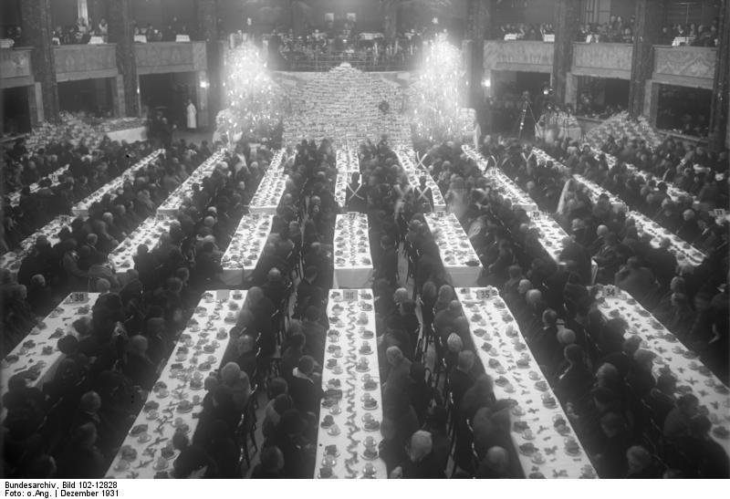 Große Weihnachtsbescherung der Heilsarmee für 2.000 bedürftige Berliner Familien. Blick in den Festsaal während der Weihnachtsbescherung, bei der jeder Kaffee und Kuchen und einen Weihnachtskorb als Gabe erhält. Bild von Bundesarchiv, Bild 102-12828 / CC-BY-SA 3.0 [CC BY-SA 3.0 de (https://creativecommons.org/licenses/by-sa/3.0/de/deed.en)]. Original auf: https://commons.wikimedia.org/wiki/File:Bundesarchiv_Bild_102-12828,_Berlin,_Bescherung_Bed%C3%BCrftiger.jpg