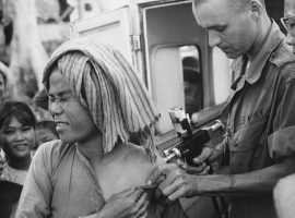 Ein Sanitäter der US Navy impft einen Flüchtling gegen Cholera in Vietnam (1966), Bildlizenz: Gemeinfrei, Bild von National Archives at College Park [Public domain]