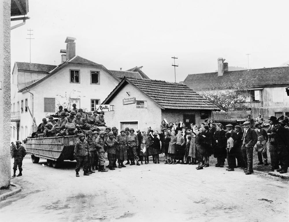 Soldaten besetzen kampflos Imst in Tirol. Der Fotograf Luis Weintraub ließ mehrere Frauen und Kinder mit weißen Bändern wirken. Das Foto wurde am 04.05.1945 aufgenommen. (c) National Archives (111-SC-267470) - mit freundlicher Genehmigung des Tyrolia-Verlags verwendet.