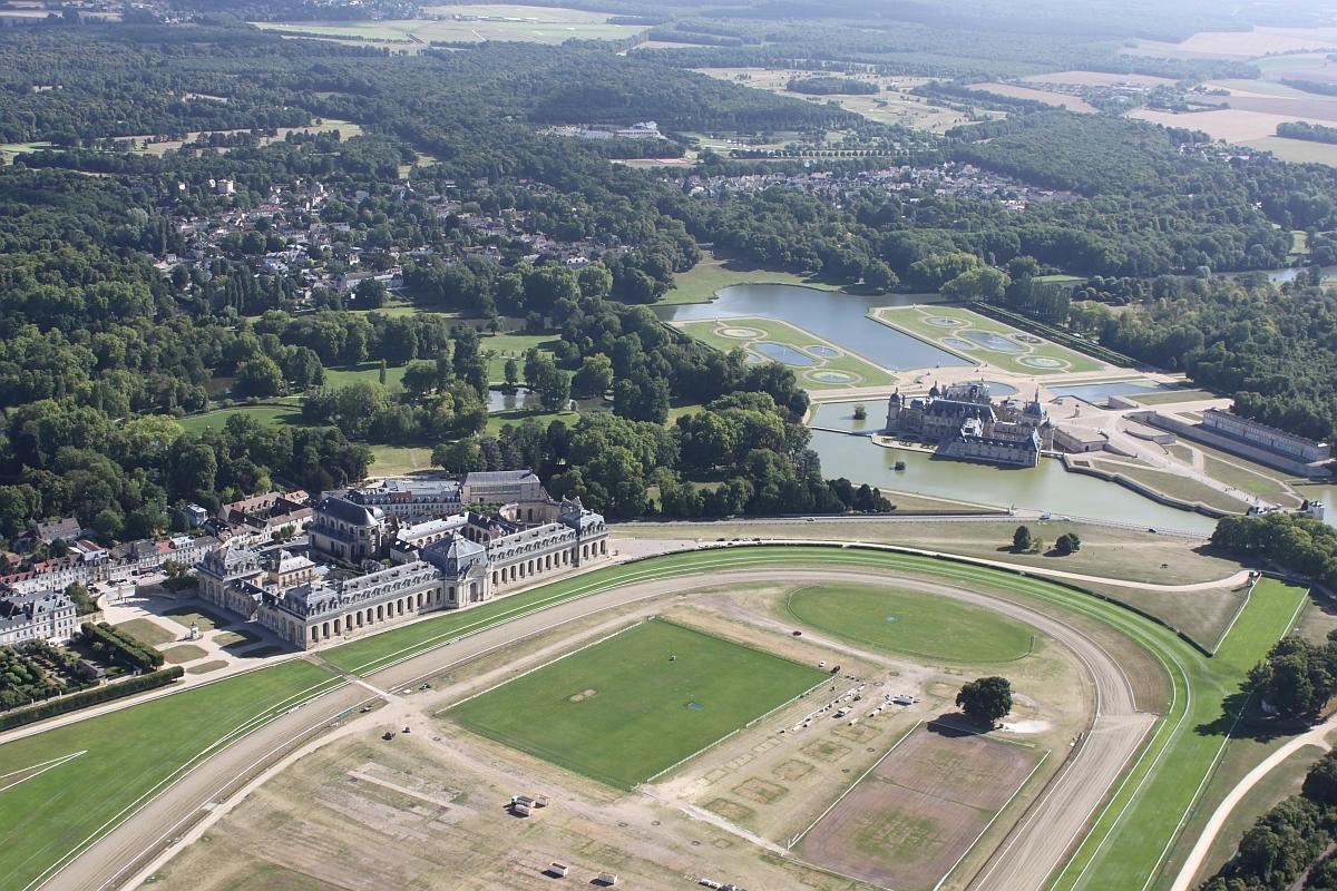 Das Luftbild macht die Größe des Schlosses im rechten Teil und der Pferdestallungen links deutlich - Lizenz: Pierre-Alain Bandinelli, CC BY-SA 4.0 , via Wikimedia Commons